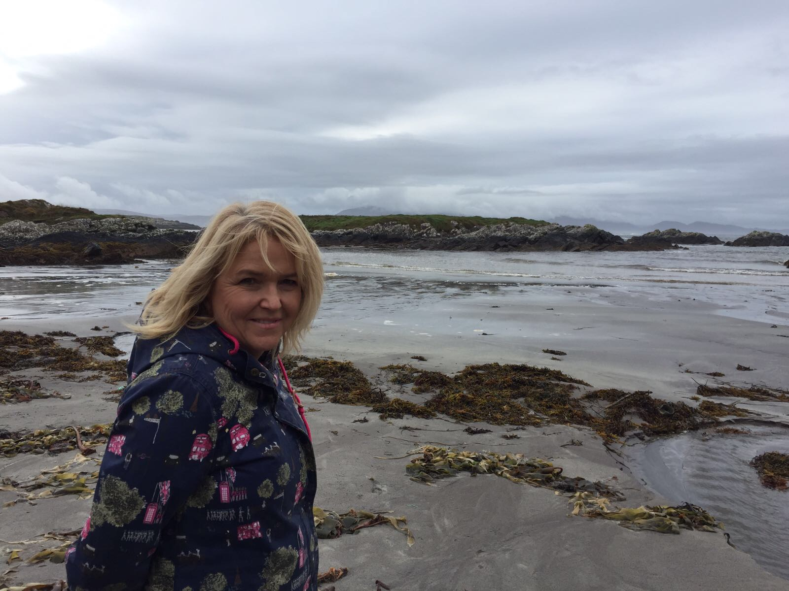 Picture of blonde woman, Sally Redmore of Sally Redmore Seaglass, standing on a beach and looking into the camera
