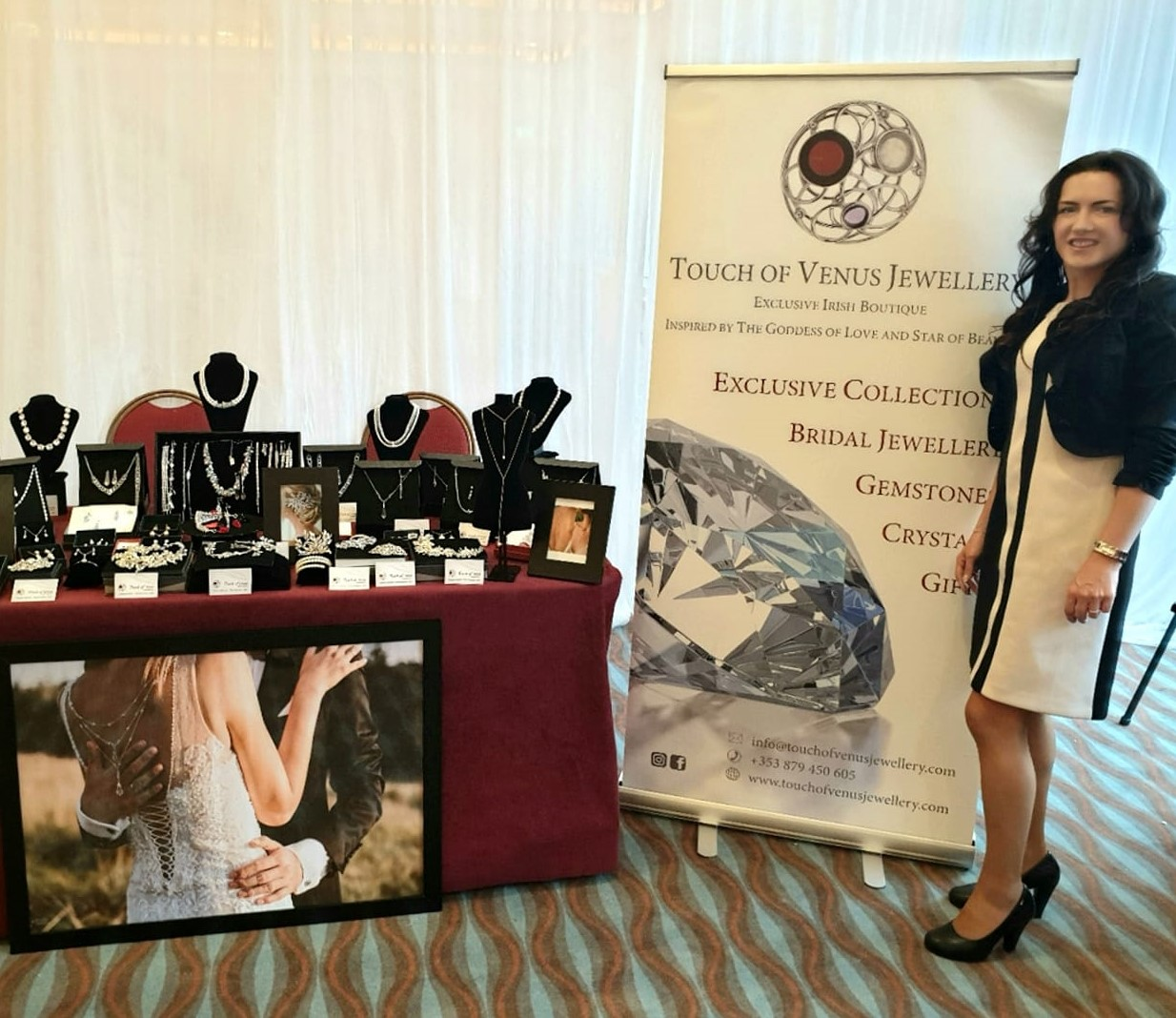 Woman standing at a sign for Touch of Venus jewellery at wedding fair